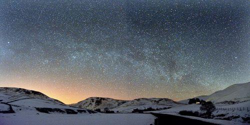 A star studded sky over snowy hills